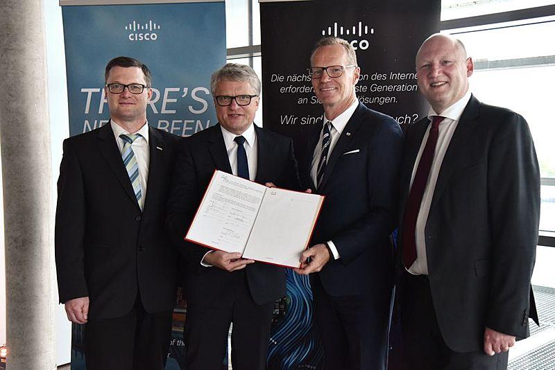 Vier Männer halten eine Mappe in die Kamera zur Verdeutlichung der Zusammenarbeit von LINZ AG TELEKOM und Cisco.