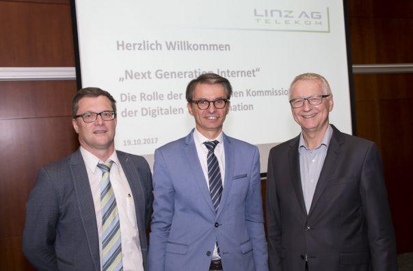 Drei Männer stehen vor einer Präsentationsleinwand.