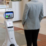 Besucherin vor dem 5G-Roboter