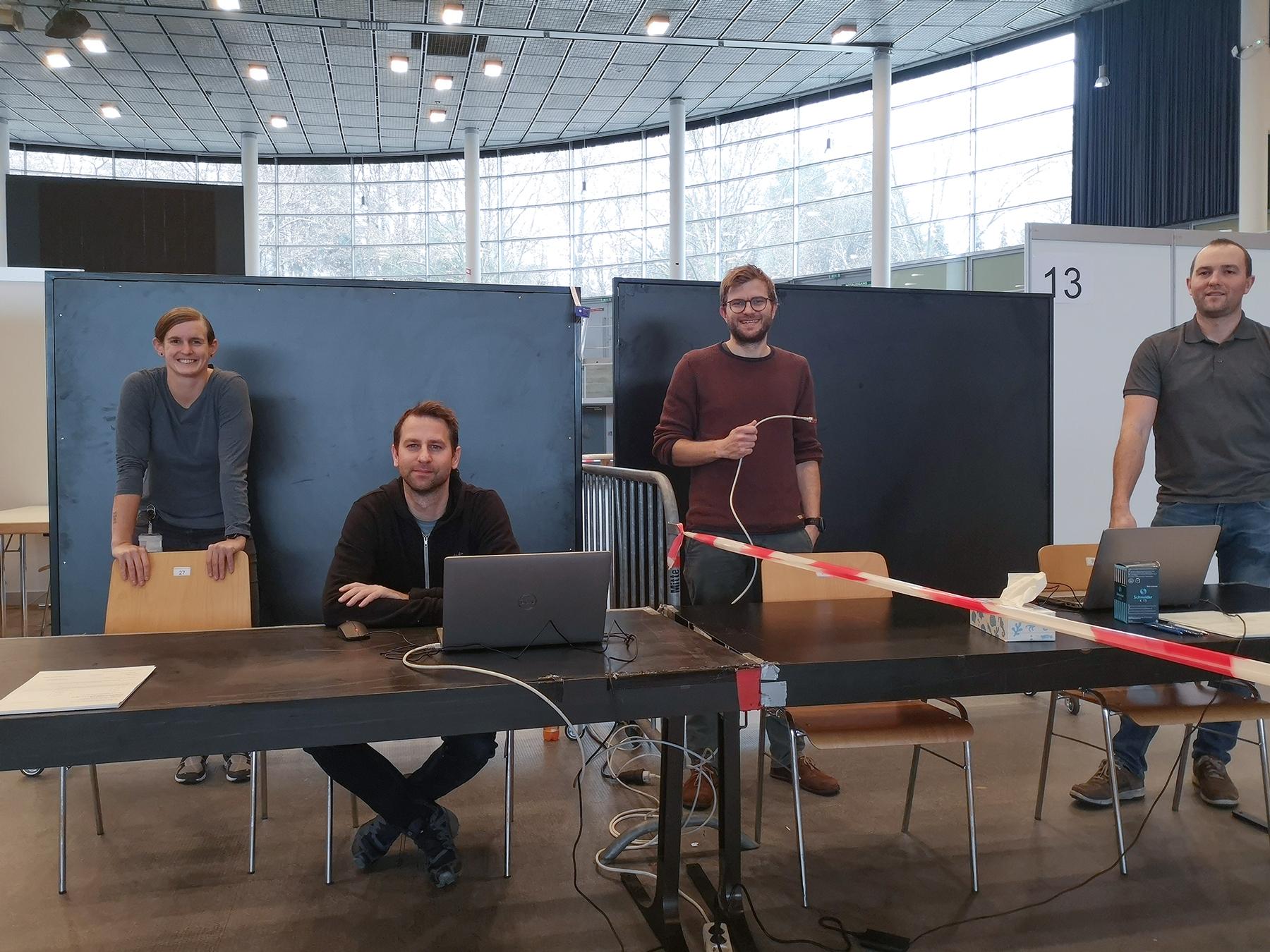 Eine Dame und drei Herren bereiten an durch Absperrband getrennten Tischen die IT-Infrastruktur für Corona-Massentestungen vor.